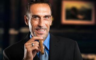 empresário maduro, fumando um charuto foto