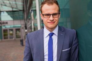 retrato do jovem empresário em frente ao bloco de escritórios. foto