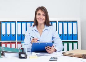 secretária feliz, com longos cabelos castanhos no trabalho no escritório