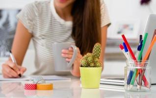 cacto em cima da mesa de escritório. mulher que trabalha em segundo plano foto
