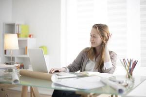 bela jovem sentada à mesa no local de trabalho foto