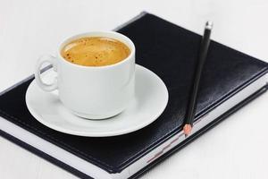 local de trabalho com diário de negócios, lápis e xícara de café