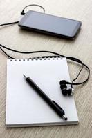 caderno de argolas aberto com telefone móvel foto