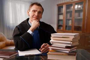 advogado ponderando seu trabalho e um grande conjunto de livros foto