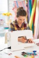 costureira trabalhando com máquina de costura foto