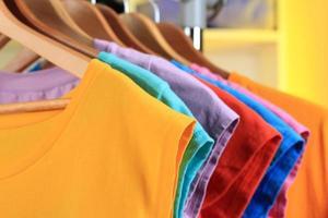 variedade de camisetas casuais em cabides de madeira foto