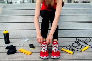 uma mulher aperta seu tênis para atividades atléticas foto