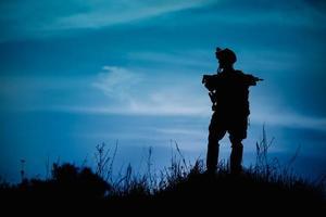 silhueta de soldado militar ou oficial com armas à noite.