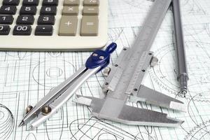 compassos de calibre vernier, calculadora, bússolas, caneta técnica e desenhos foto