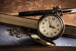 relógio de bolso com caneta e livro antigo. foto