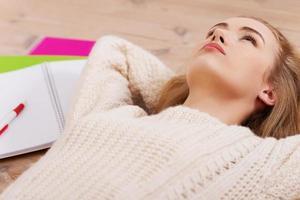 mulher jovem bonita estudante está deitado no chão de madeira foto