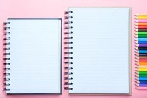 caderno e lápis de cor sobre fundo rosa foto