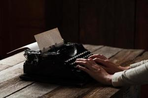 mãos escrevendo na velha máquina de escrever sobre fundo de madeira foto