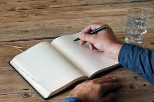 homem escreve em um caderno em branco closeup foto