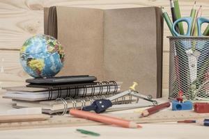 vários artigos de papelaria e notebook na mesa para a escola foto