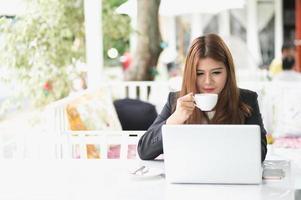 mulher asiática no café com laptop e café, conceito do negócio foto