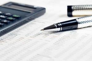 caneta de negócios, calculadora na ficha financeira