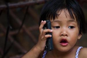 menina asiática que fala ao telefone foto