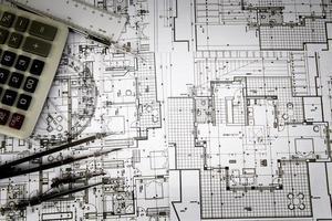 projeto arquitetônico, par de bússolas, transferidor e calculadora foto