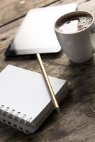 tablet, telefone, bloco de notas e café na mesa de madeira foto