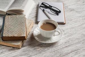 pilha de livros, bloco de notas, copos e uma xícara de cacau foto