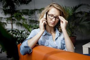aluno pensando ou pensando em algo. segurando os óculos na mão foto