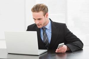 elegante empresário usando laptop e telefone móvel foto