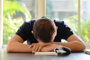 jovem dormindo em cima da mesa com o livro aberto foto