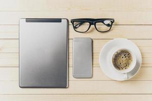 telefone celular e tablet com notebook em cima da mesa foto