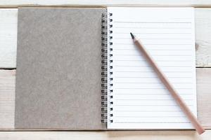 caderno aberto e lápis na mesa de madeira foto