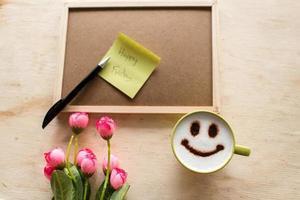 feliz sexta-feira na nota de papel com café no quadro de avisos foto
