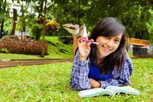 menina asiática sorrindo com livro e estudar no parque foto