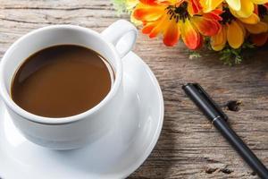 xícara de café, caneta na mesa de madeira foto