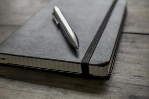 caderno de couro com caneta prata sobre uma mesa de madeira foto