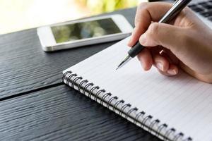mão segure uma caneta escrevendo no caderno foto