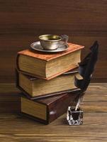 livros antigos e caneta sobre uma mesa de madeira foto