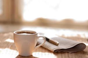 xícara de café preto, jornal e uma caneta foto