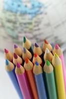 lápis coloridos com globo no fundo foto