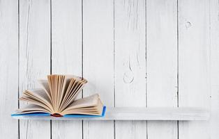 o livro aberto em uma prateleira de madeira. foto