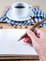 mão escrevendo no notebook com fundo de xícara de café foto