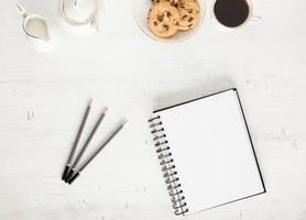 bloco de notas, lápis na mesa branca com café