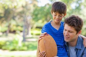menino e seu pai olham para o futebol foto