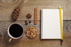 caderno e café com deliciosos biscoitos foto
