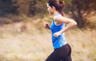 jovem mulher correndo na natureza ao nascer do sol