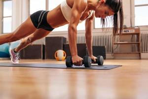 mulher de aptidão fazendo flexões exercício com halteres foto