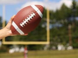 futebol americano na mão sobre o campo com trave foto