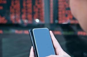 negociação de ações no celular perto da placa de câmbio