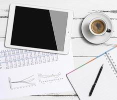 tablet digital e xícara de café na mesa de madeira foto