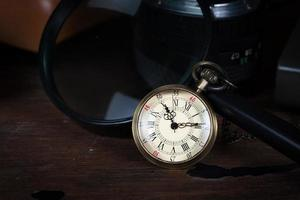 conceito de tempo, relógio antigo e lupa na mesa de madeira