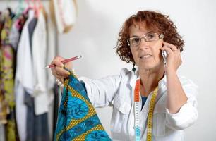 costureira de meia-idade, falando ao telefone com seu cliente foto
